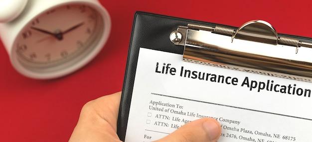 Mann hält lebensversicherungsantragsformular. schreibtischhintergrund mit alam-uhr. schutz und sicheres lebenskonzept foto- und bannerdesign