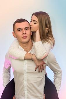 Mann hält mädchen auf seinem rücken, während sie ihn sanft küsst