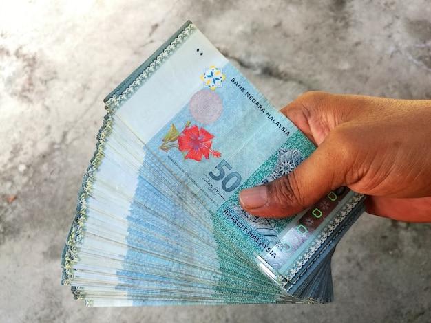 Mann hält malaysische ringgitbanknoten auf grauem strukturiertem hintergrund