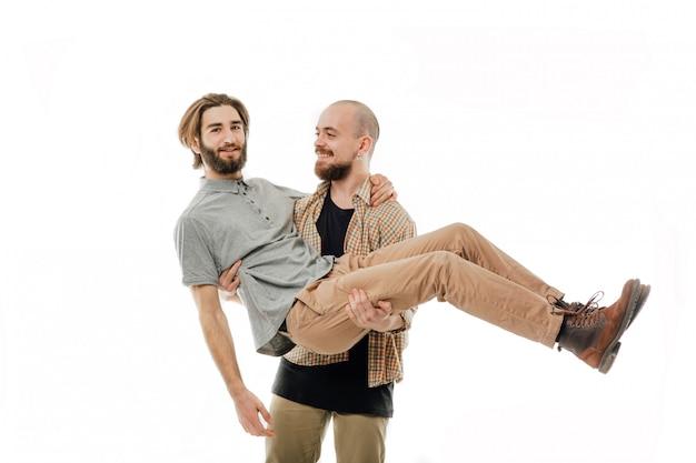 Mann hält mann in seinen händen, arme, trägt einen mann in seinen händen. schwules paar, isolierter leerraum, kopierraum, isoliert