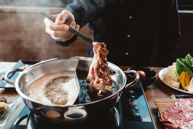 Mann hält mittlere seltene scheibe wagyu a5 rindfleisch aus shabu shoyu suppe basis von essstäbchen mit dampf.