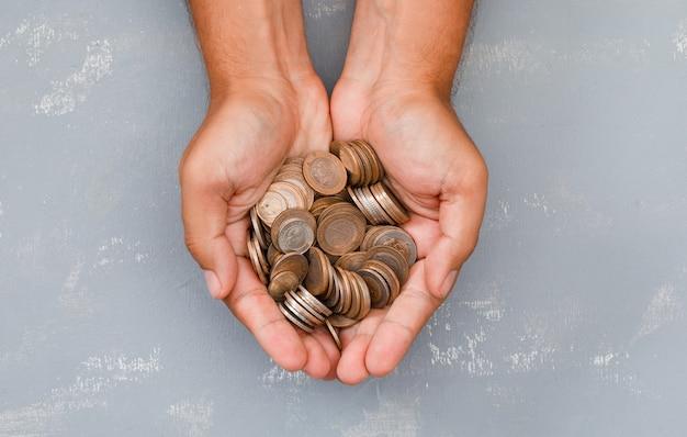 Mann hält münzen in der handfläche.