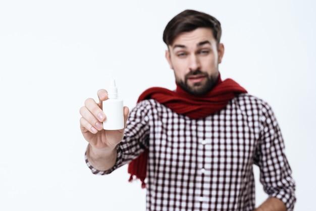 Mann hält nasentropfen auf weißem hintergrund.