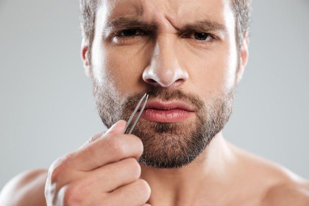 Mann hält pinzette und runzelt die stirn