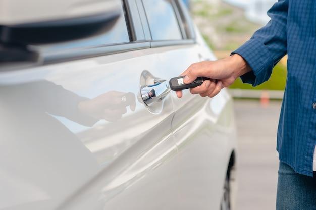Mann hält schlüssel, der autotür öffnet