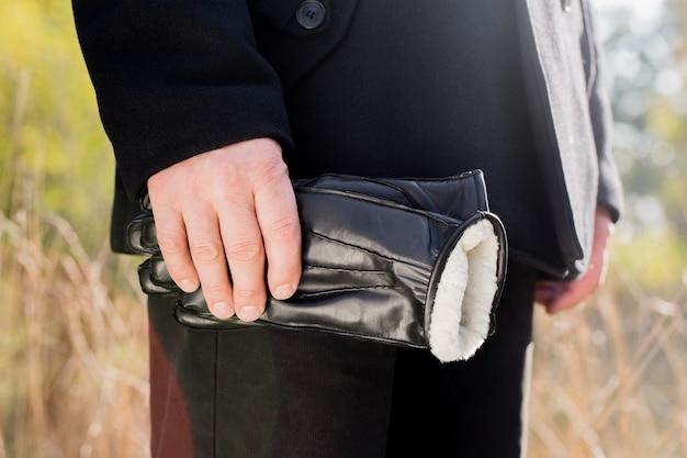 Mann hält schwarze lederhandschuhe in seinen händen.