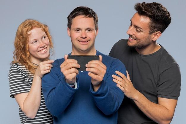 Mann hält sein telefon für ein foto mit seinen freunden