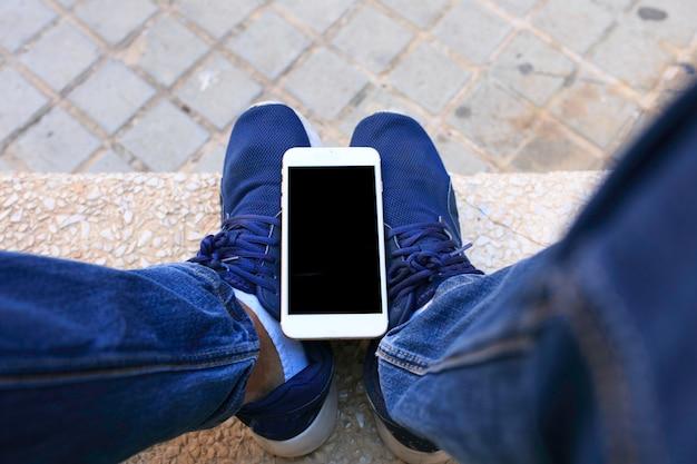 Mann hält sein telefon in ihren beinen