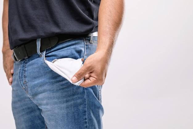 Mann hält seine hosentasche, um kein geld darin zu zeigen