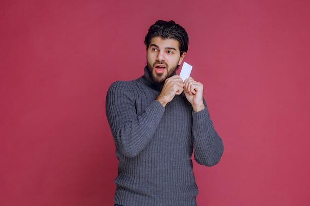 Mann hält seine visitenkarte, fühlt sich sehr positiv und selbstbewusst.