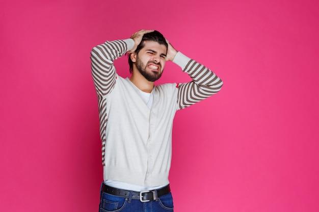 Mann hält seinen kopf, als er erschöpft ist oder kopfschmerzen hat.