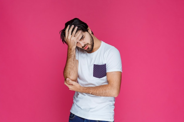 Mann hält seinen kopf, als hätte er kopfschmerzen oder ein großes problem.