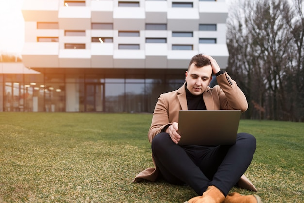Mann hält seinen kopf, während er an einem laptop arbeitet