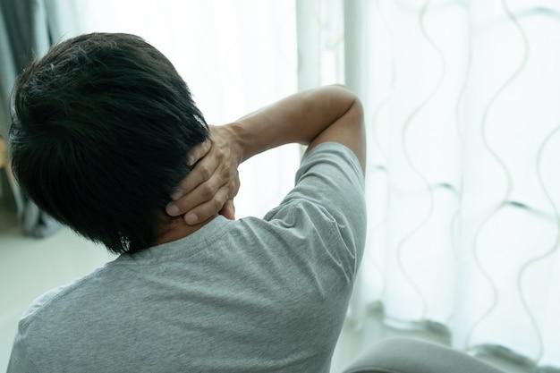 Mann hält seinen nacken vor schmerzen. medizinisches konzept