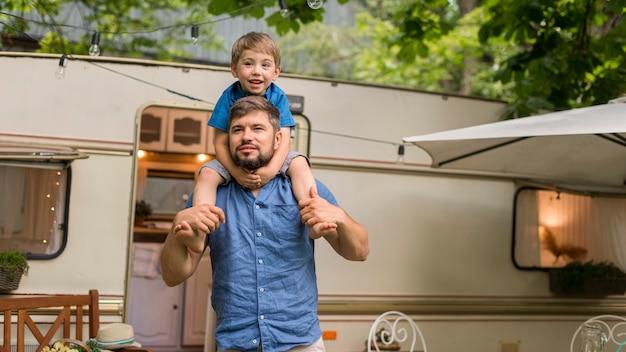 Mann hält seinen sohn auf seinen schultern neben einem wohnwagen mit kopierraum