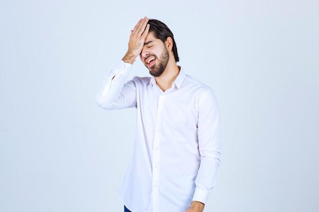 Mann hält sich den kopf wegen kopfschmerzen oder erschöpfung