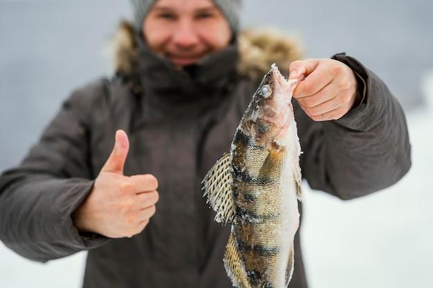 Mann hält siegreich einen fisch, den er gefangen hat