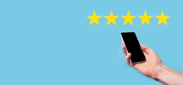 Mann hält smartphone in händen und gibt positive bewertung, symbol fünf-sterne-symbol, um die bewertung des unternehmenskonzepts auf blauem hintergrund zu erhöhen. kundenservice erfahrung und geschäftszufriedenheit umfrage.