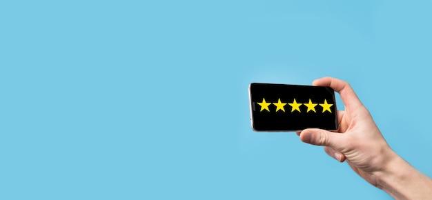 Mann hält smartphone in händen und gibt positive bewertung, symbol fünf-sterne-symbol, um die bewertung des unternehmenskonzepts auf blauer oberfläche zu erhöhen