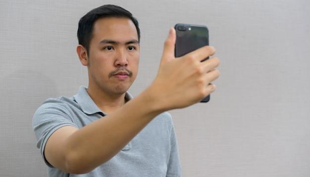 Mann hält smartphone und verwendet gesichtserkennungstechnologie für das entsperren und den zugriff