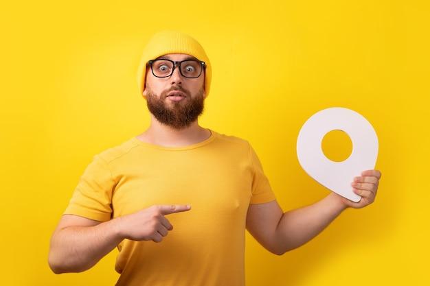Mann hält standortmarkierung und zeigt auf ihn über gelbem hintergrund, konzeptnavigation und erkundung