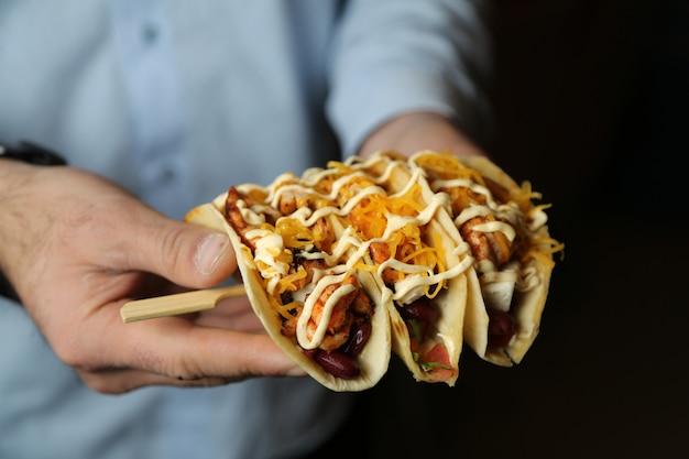 Mann hält stöcke mit tacos hühnerbohnen tomaten pfeffer käse Kostenlose Fotos