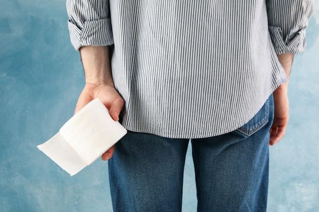 Mann hält toilettenpapier auf blau, nahaufnahme