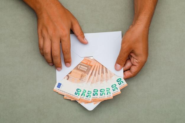 Mann hält umschlag voller banknoten.