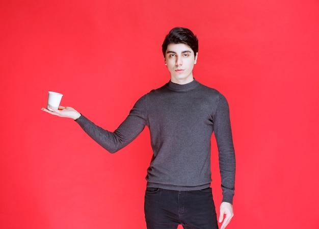 Mann hält und demonstriert eine tasse getränk