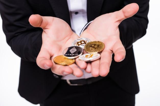 Mann hält verschiedene kryptomünzen in seinen händen auf weiß