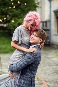 Mann hält zarte frau mit dem rosa haar, das gegen den wind steht