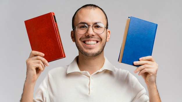 Mann hält zwei bücher und lacht