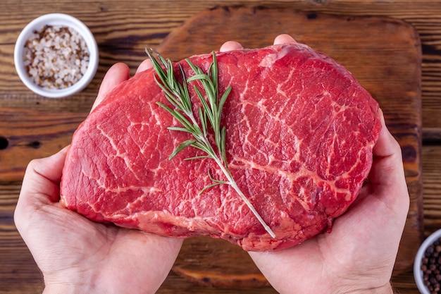 Mann-hände, die ein rohes frisches rindfleisch-steak mit rosemary über schalen mit kräutern halten
