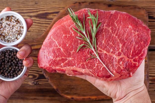 Mann-hände, die ein rohes frisches steak mit rosemary und schalen mit kräutern halten