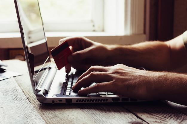 Mann-hände, die kreditkarte halten und laptop am abend verwenden.