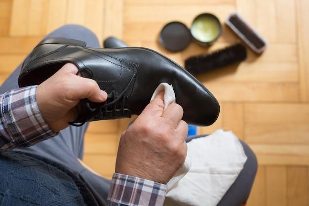 Mann hände reinigen seine schuhe mit einem lappen und schuhwachs für einen besseren zustand seiner schuhe, polieren schuhe