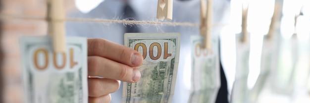 Mann hängen hundert dollar mit wäscheklammer am seil.