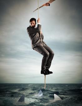 Mann hängt an einem von einer säge geschnittenen seil