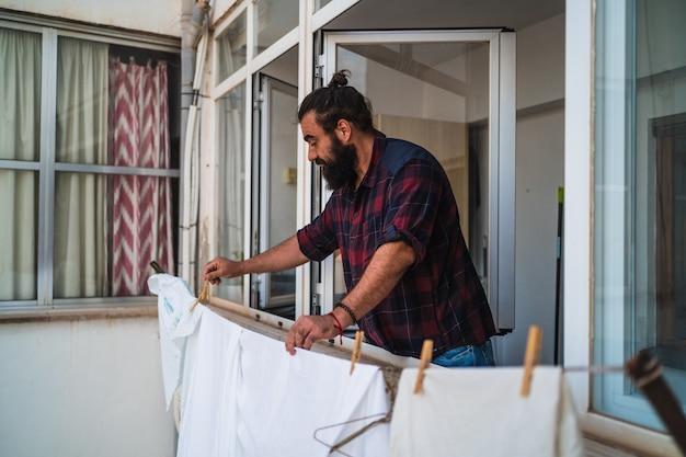 Mann hängt an seinen kleidern mit wäscheklammern. mann, der an seinen kleidern zu hause mit wäscheklammern hängt