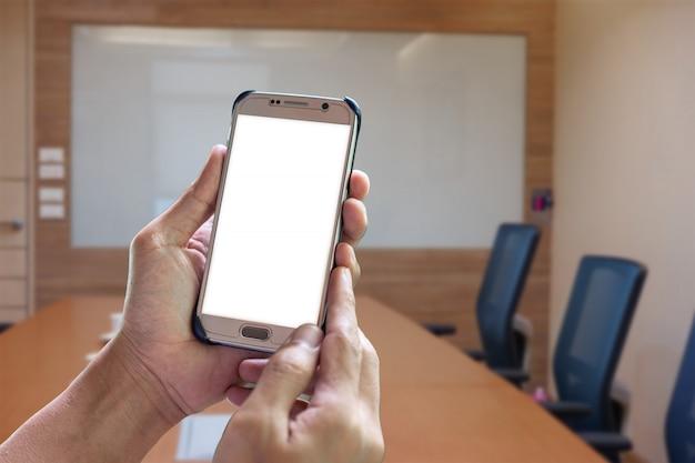 Mann halten einen weißen bildschirm des intelligenten telefons im konferenzzimmer