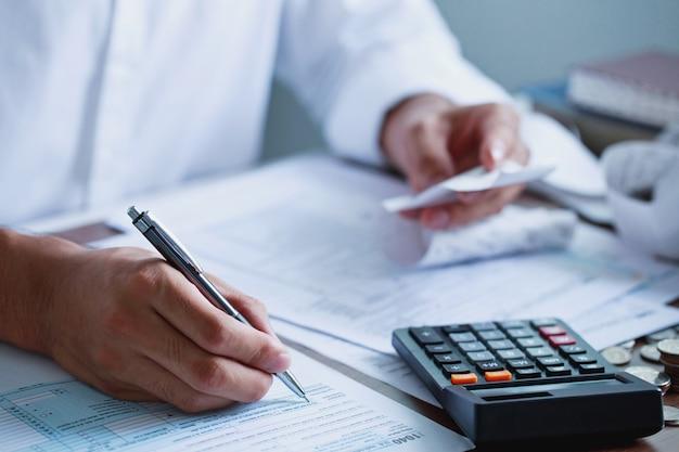 Mann hand ausfüllen us-steuerformular steuerformular uns geschäftseinkommensbüro finanzdokumentsteuerkonzept verlust