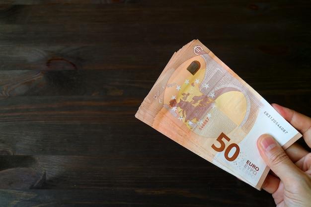 Mann-hand, die 50 eurobanknoten auf dunkelbraunem holz hält