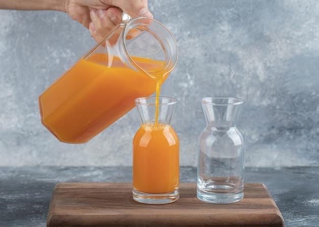 Mann hand gießt orangensaft in glas auf marmortisch.