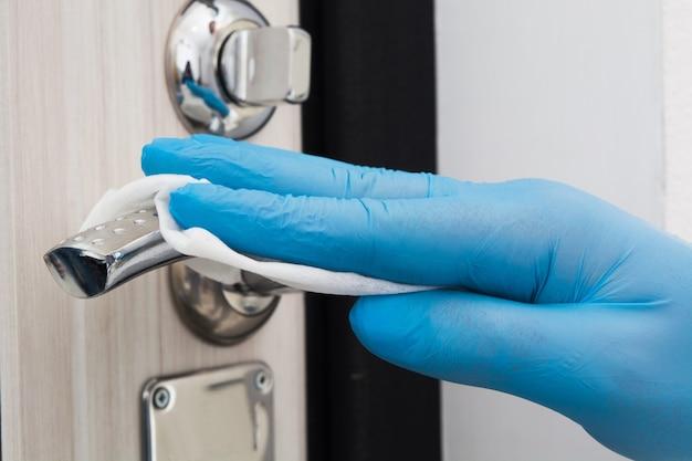 Mann hand in blauen handschuh reinigung türknauf mit einweg serviette quarantänezeit