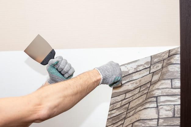 Mann hand reißen alte leichte tapete von der wand ab. vorbereitung für reparaturarbeiten zu hause. entfernen der tapete mit einem spatel, der prozess der aktualisierung der wandraumreparatur. speicherplatz kopieren