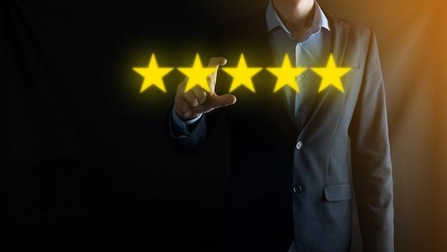 Mann hand smartphone telefon auf fünf sterne ausgezeichnete bewertung. zeigen fünf sterne symbol, um die bewertung des unternehmens zu erhöhen. überprüfung, bewertung oder ranking, bewertung und klassifizierung konzept erhöhen