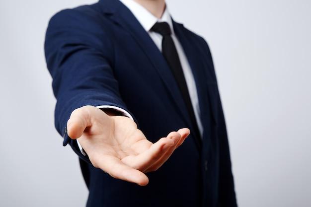 Mann hand tragen anzug zeigt eine zeichenwand, nahaufnahme, geschäftskonzept, gesten, einladend, helfende hand.