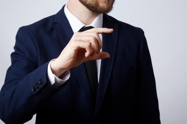 Mann hand tragen anzug zeigt eine zeichenwand, nahaufnahme, geschäftskonzept, gesten, zunehmendes zeichen.