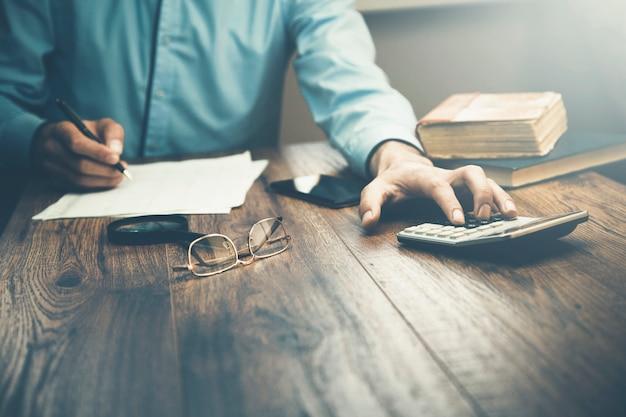 Mann handrechner und dokumente