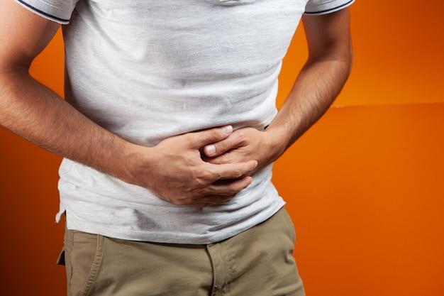 Mann hat bauchschmerzen auf orangem hintergrund
